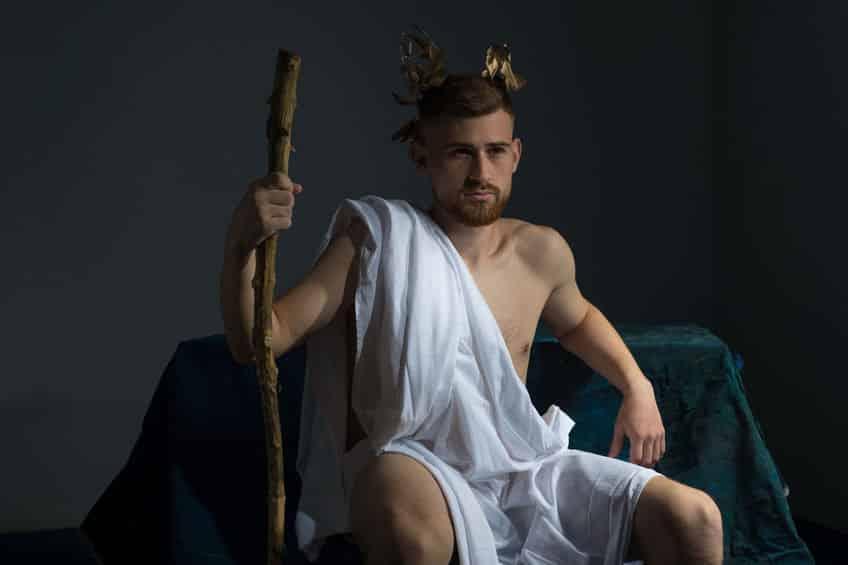 Portrait du dieu grec antique Olympe, en vêtements blancs, avec une couronne sur la tête, tient un bâton, assis sur un banc sombre. Sur un fond gris.