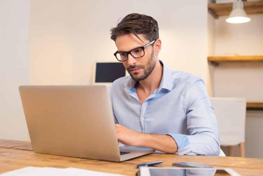 Jeune employé de bureau décontracté travaillant sur un ordinateur portable