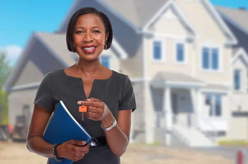 Agent immobilier afro-américain souriant avec une clé de maison
